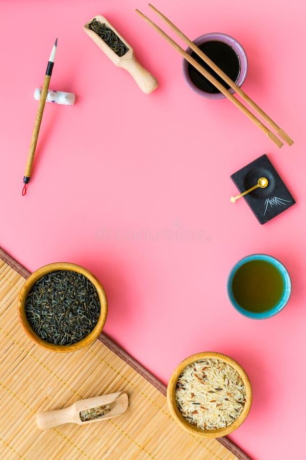 中国传统标志概念 茶,米,象形文字标志,bambootabe席子,筷子,在桃红色的大豆sause 库存图片