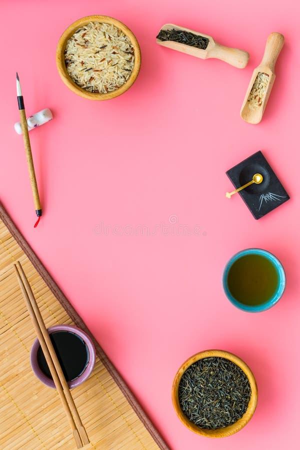 中国传统标志概念 茶,米,象形文字爱,竹碗碟衬垫,筷子,在桃红色的大豆sause 库存照片
