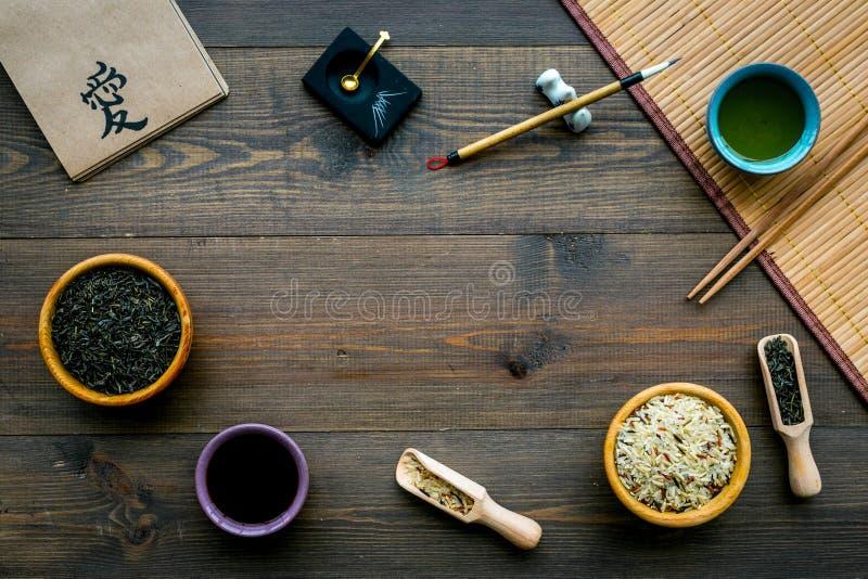 中国传统标志概念 茶,米,象形文字爱,竹碗碟衬垫,筷子,在黑暗木的大豆sause 免版税图库摄影