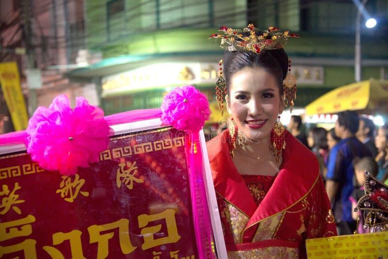 中国俏丽的神仙的夫人拿着在游行的一块牌在街道上在农历新年庆祝 免版税库存图片
