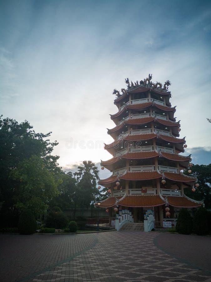 中国八角型塔在豪华的绿叶中的庭院里 库存图片