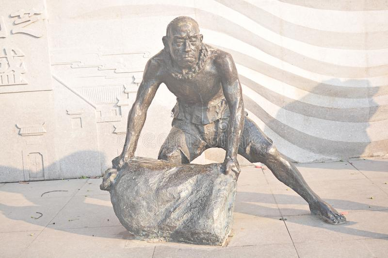 中国古老人后面沙子袋子石雕刻的艺术古铜色雕象 免版税库存图片