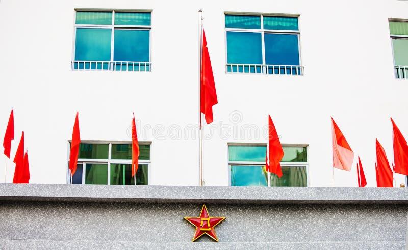 中国国徽和旗子在大厦 免版税库存照片