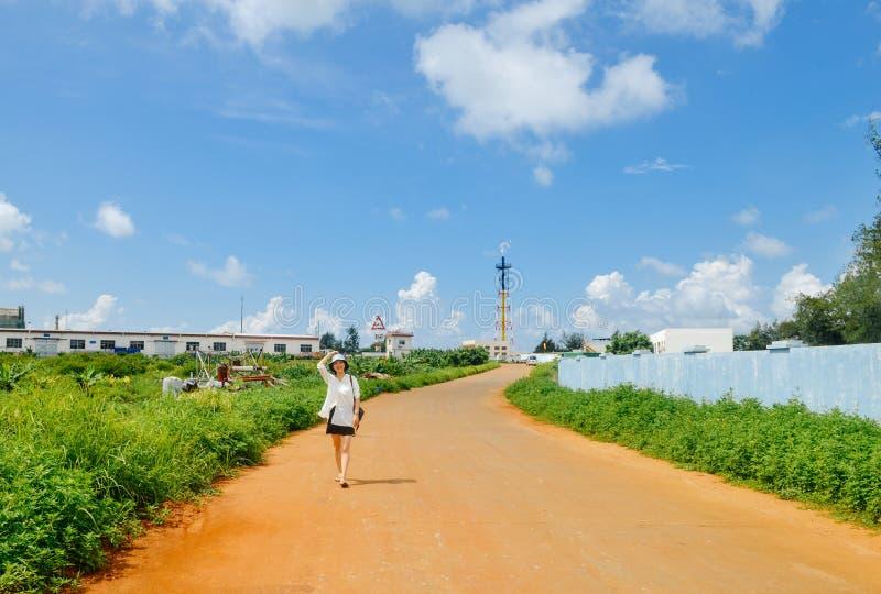 中国女孩在乡下公路走到石油化工厂 库存照片
