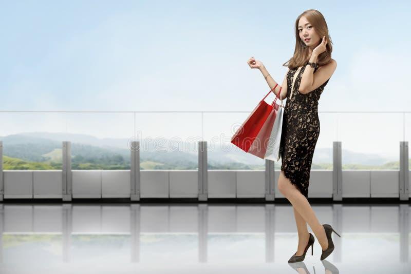 中国妇女画象拿着购物袋的黑礼服的 库存照片