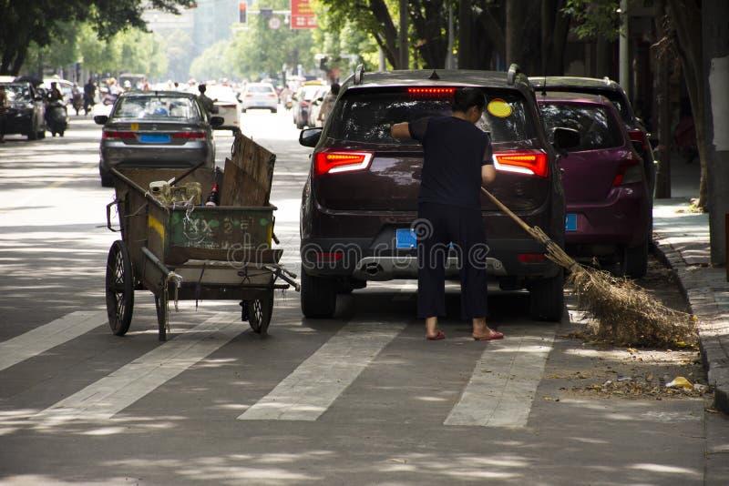 中国妇女街道清扫车工作干净和保留垃圾和推挤在走与交通的路和人民的垃圾推车 免版税库存图片