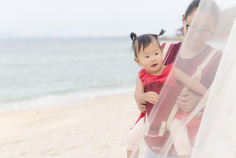中国妈妈和女孩在海滩的小型航空母舰假期 免版税图库摄影