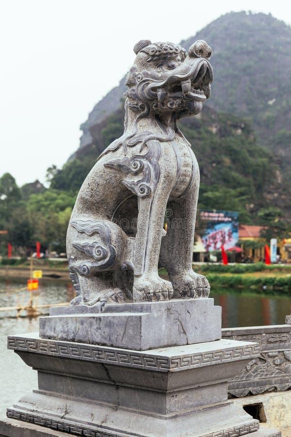 中国式狮子在Trang附近的石头雕塑与山的风景复合体在背景中在夏天在Ninh Binh,越南 免版税库存图片