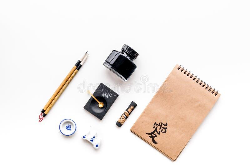中国或日本书法样式 在工艺纸笔记本和书写辅助部件的象形文字在白色背景 免版税库存图片