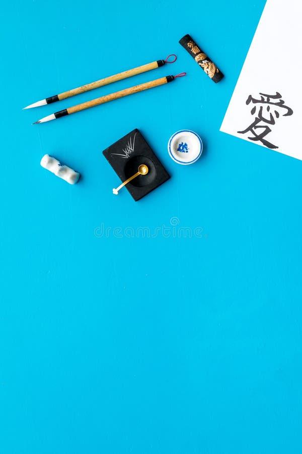 中国或日本书法概念 在传统书面辅助部件附近的象形文字在蓝色背景顶视图 免版税库存图片