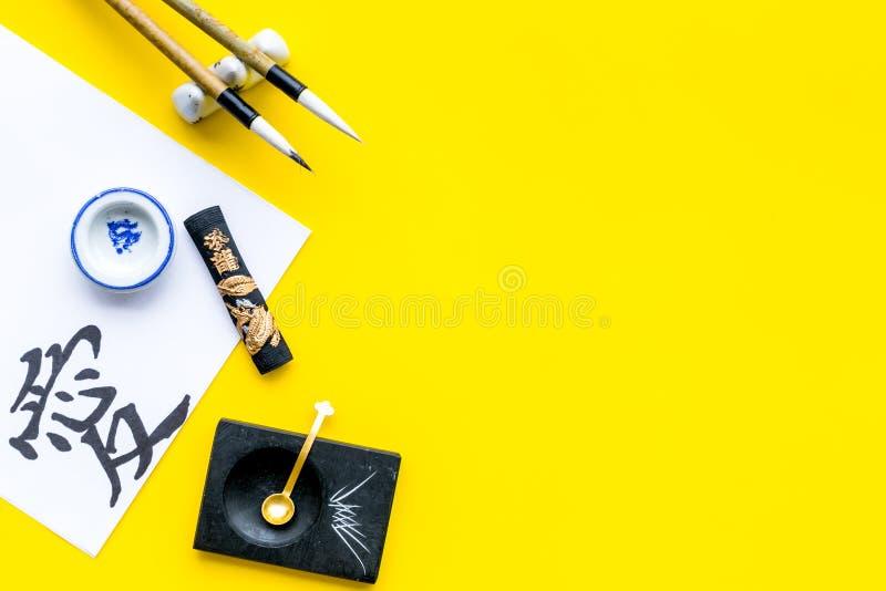 中国或日本书法概念 在传统书面辅助部件附近的象形文字在黄色背景顶视图 免版税库存照片