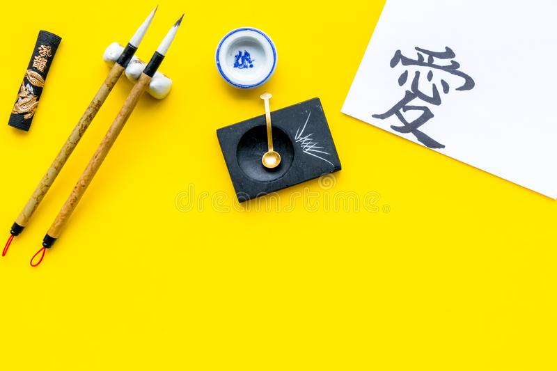 中国或日本书法概念 在传统书面辅助部件附近的象形文字在黄色背景顶视图 免版税库存图片
