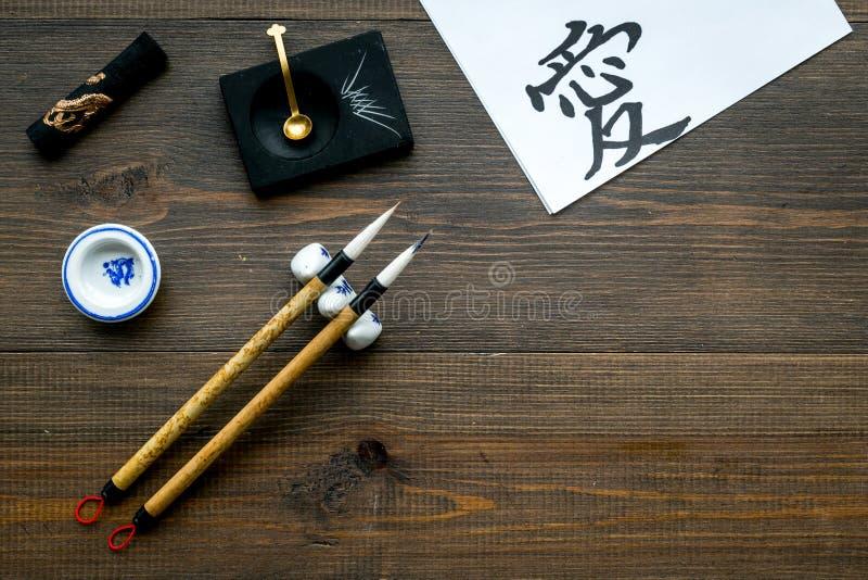 中国或日本书法概念 在传统书面辅助部件附近的象形文字在黑暗的木背景上面 图库摄影