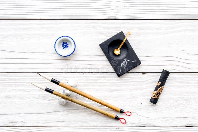 中国或日本书法的辅助部件 特别书写笔,在白色木背景顶视图的墨水 免版税库存照片
