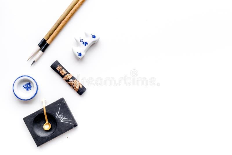 中国或日本书法的辅助部件 特别书写笔,在白色背景顶视图拷贝空间的墨水 图库摄影