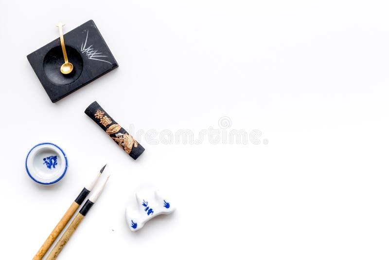 中国或日本书法的辅助部件 特别书写笔,在白色背景顶视图拷贝空间的墨水 库存照片
