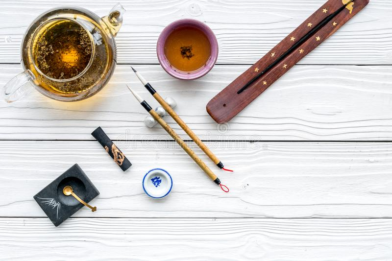 中国或日本传统 书法和茶道概念 特别书写笔、墨水在茶壶附近和杯子  图库摄影