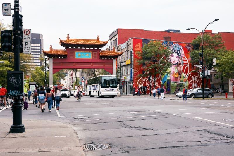 中国曲拱门、人民和交通在中国镇入口在圣劳伦特街道上在蒙特利尔,魁北克,加拿大 免版税库存照片