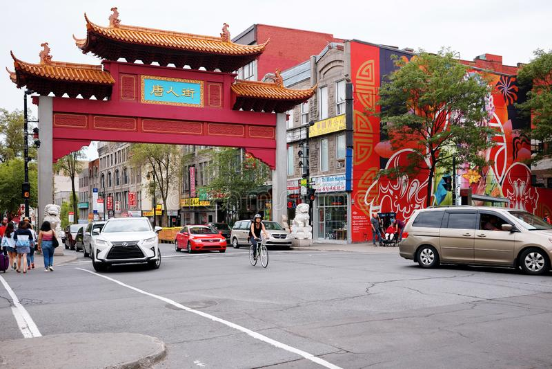 中国曲拱门、人民和交通在中国镇入口在圣劳伦特街道上在蒙特利尔,魁北克,加拿大 库存照片