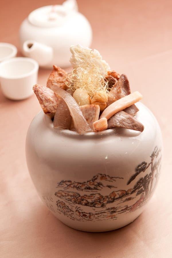 中国清凉茶用干蘑菇和药物在白色罐 免版税库存照片