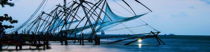 中国渔网在科钦,喀拉拉,日落的印度 五颜六色的多云天空 免版税库存图片