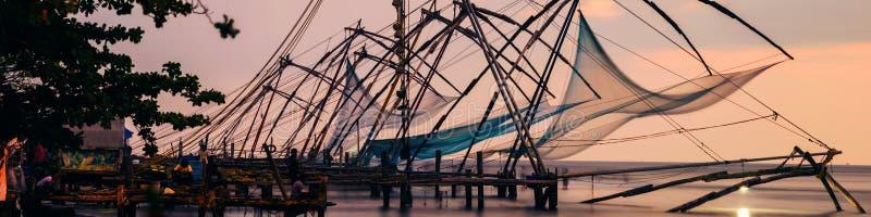 中国渔网在科钦,喀拉拉,日落的印度 五颜六色的多云天空 库存图片