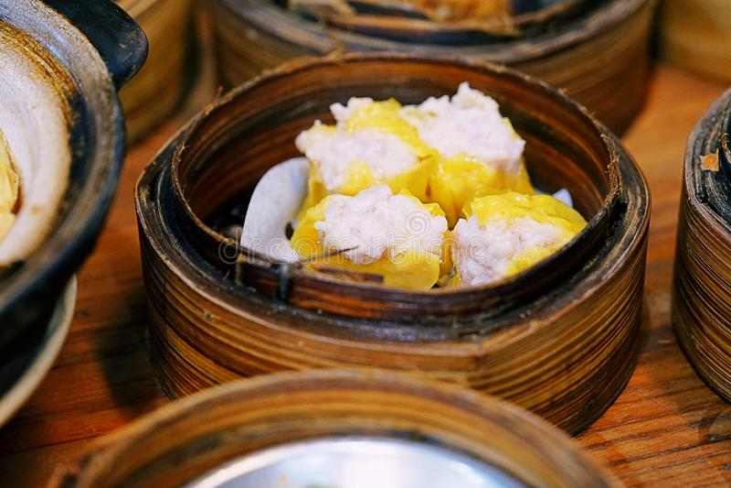 中国烹调Shumai,热和蒸汽的昏暗的sim或者蒸的中国猪肉饺子在火轮篮子被设置了 图库摄影