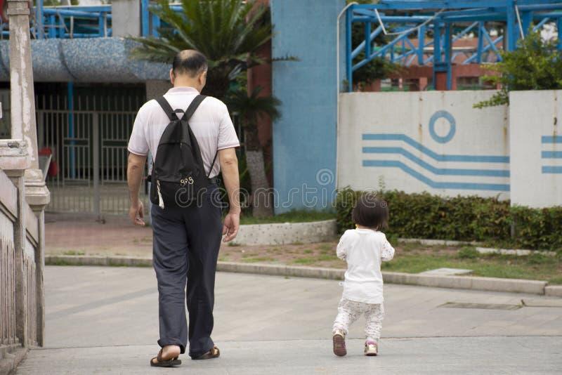 中国老人人民走的放松与婴孩在中山公园的庭院里在汕头或Swatow市在广东,中国 库存照片