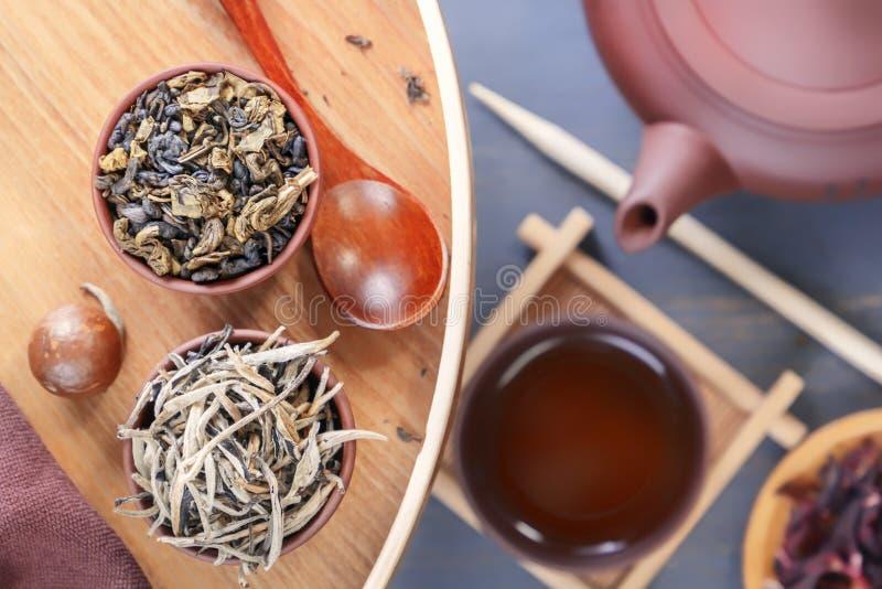 中国茶道、绿茶的几种类型,一个陶瓷茶壶和杯子的属性在一张灰色木桌上站立 免版税库存图片