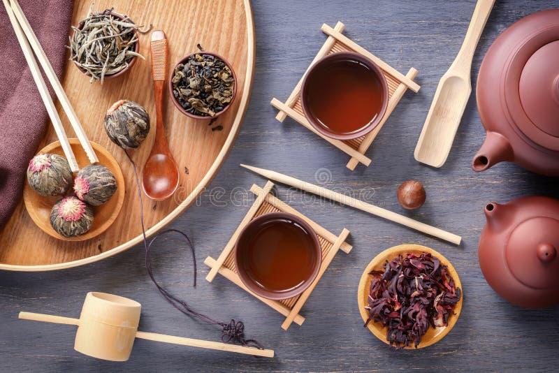 中国茶道、绿茶的几种类型,一个陶瓷茶壶和杯子的属性在一张灰色木桌上站立 图库摄影