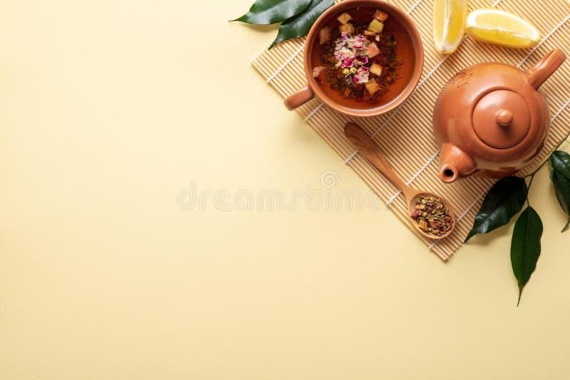 中国茶道 陶瓷茶壶,茶杯,绿色叶子,木匙子用在竹席子的干茶在黄色背景 顶层 库存照片