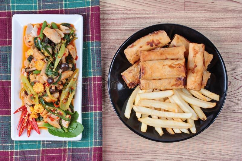 中国菜节日食物,与混杂的菜的油煎的蓬蒿供食了被油炸的春卷和炸薯条 免版税库存图片