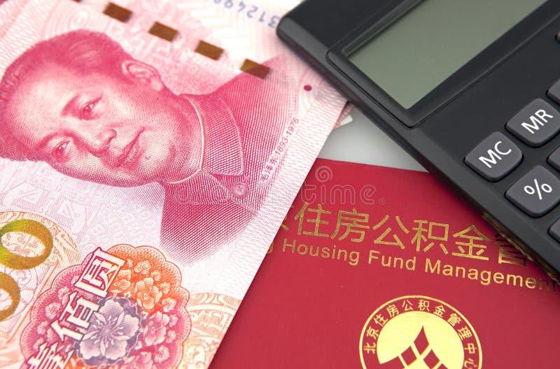 中国钞票、计算器和住房储积资助在白色背景的存折 免版税库存照片