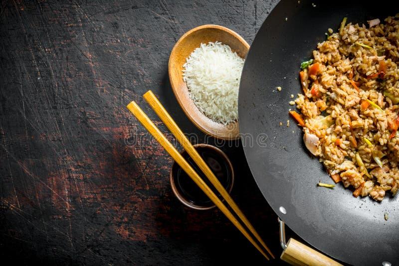 中国铁锅 在铁锅平底锅的煮熟的米和在板材的未煮过的米 免版税库存照片