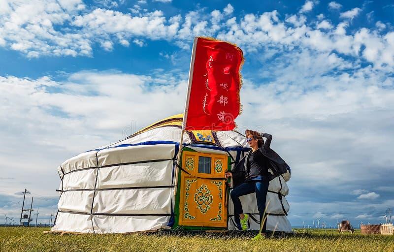 中国-在一yurt前面的母牛女孩在内蒙古 免版税库存图片