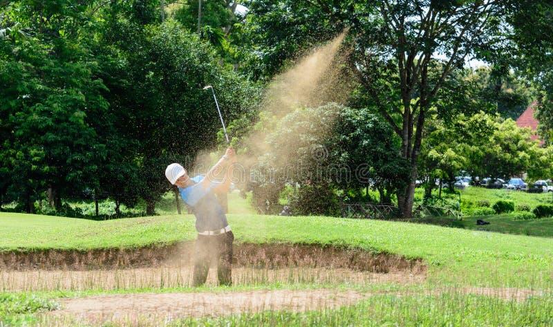 击中在沙子的亚裔英俊的高尔夫球运动员球 速度原因 免版税库存图片