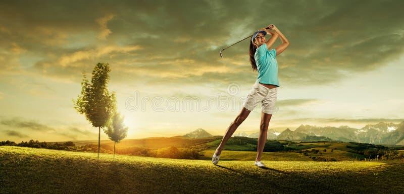 击中在背景风景的女子高尔夫球运动员球 免版税库存照片