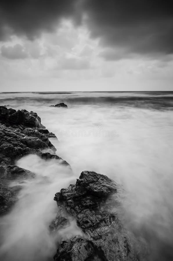 击中在黑暗的云彩背景的软的波浪流程沙滩 软的焦点图象由于长的曝光射击 免版税库存照片