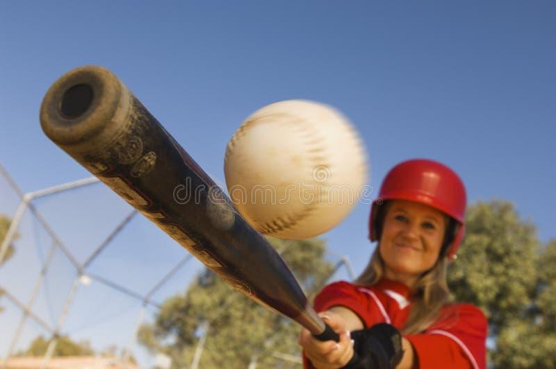 击中射击的女性棒球运动员 免版税库存图片