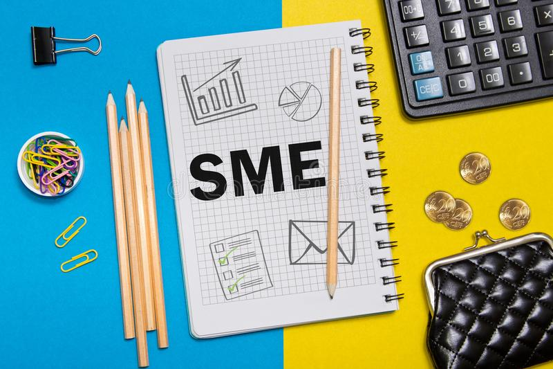 中小企业,在笔记本的SME笔记在一个商人的书桌上在办公室 企业概念SME 免版税库存图片