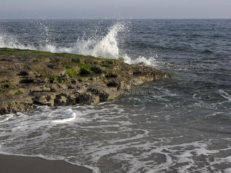 击中岩石岸的海波浪 免版税图库摄影