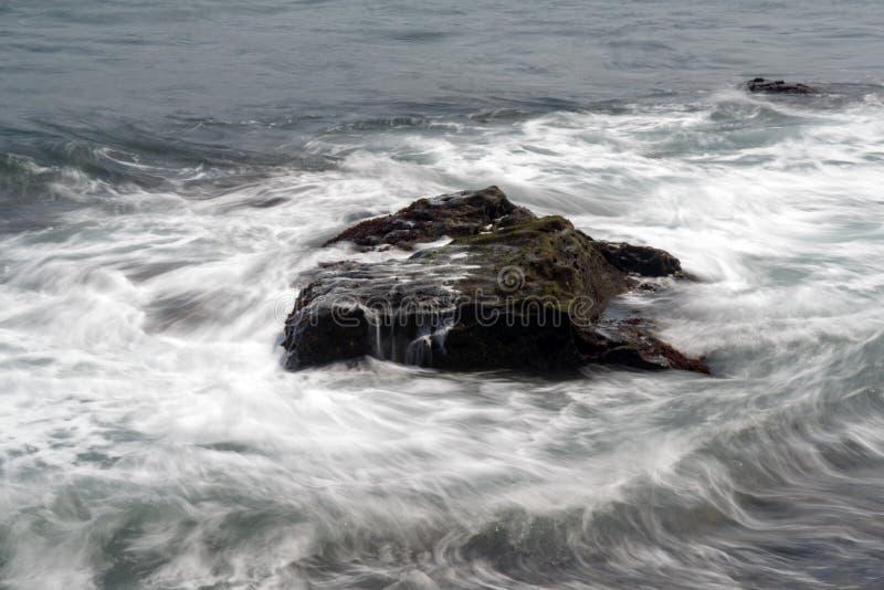 击中岸岩石的海波浪 免版税图库摄影