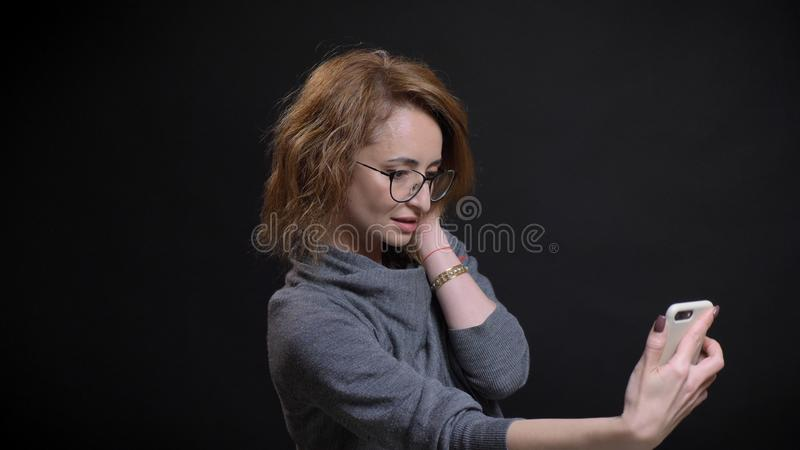 中年侈奢的红发女性特写镜头画象采取在电话的selfies和摆在前面的玻璃的 图库摄影