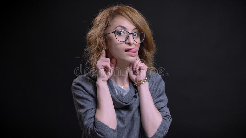 中年侈奢的红头发人特写镜头画象女性在做一滑稽表情和显示的玻璃  库存图片