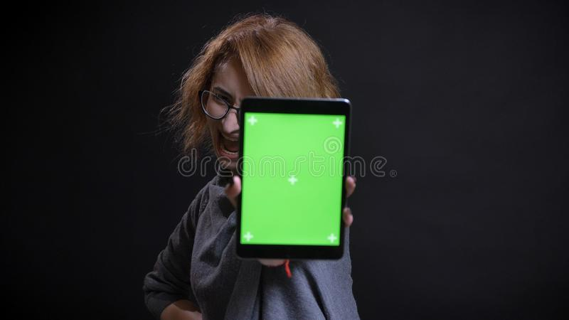 中年侈奢的红头发人特写镜头画象女性在玻璃使用片剂和显示绿色屏幕 库存图片