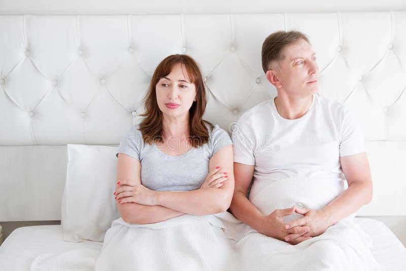 中年加上在关系的争吵问题在卧室的床上 家庭生活 复制空间 免版税图库摄影