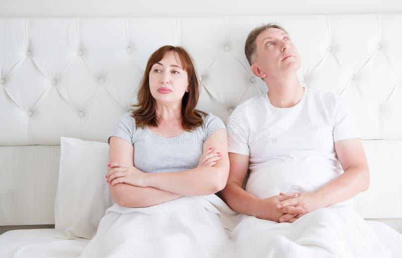 中年加上在关系的争吵问题在床上 家庭生活 复制空间 库存图片