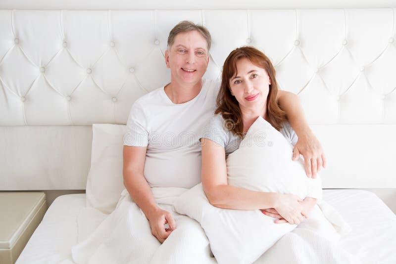中年加上坐在床上的皱痕 模板空白的T恤杉 妇女和人在卧室 健康生活方式和睡眠 库存照片
