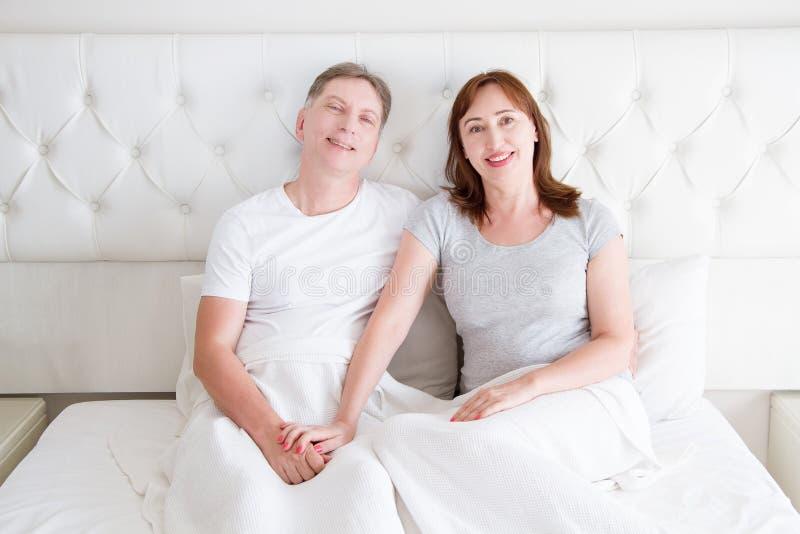 中年加上坐在床上的皱痕 模板空白的T恤杉 妇女和人在卧室 健康生活方式和睡眠 免版税库存照片