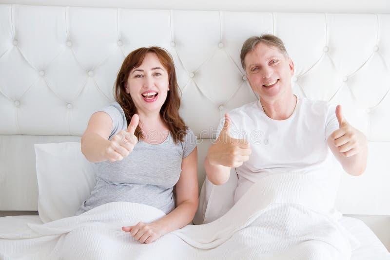 中年夫妇在在床上和显示大赞许的卧室 幸福家庭生活和关系 复制空间 图库摄影